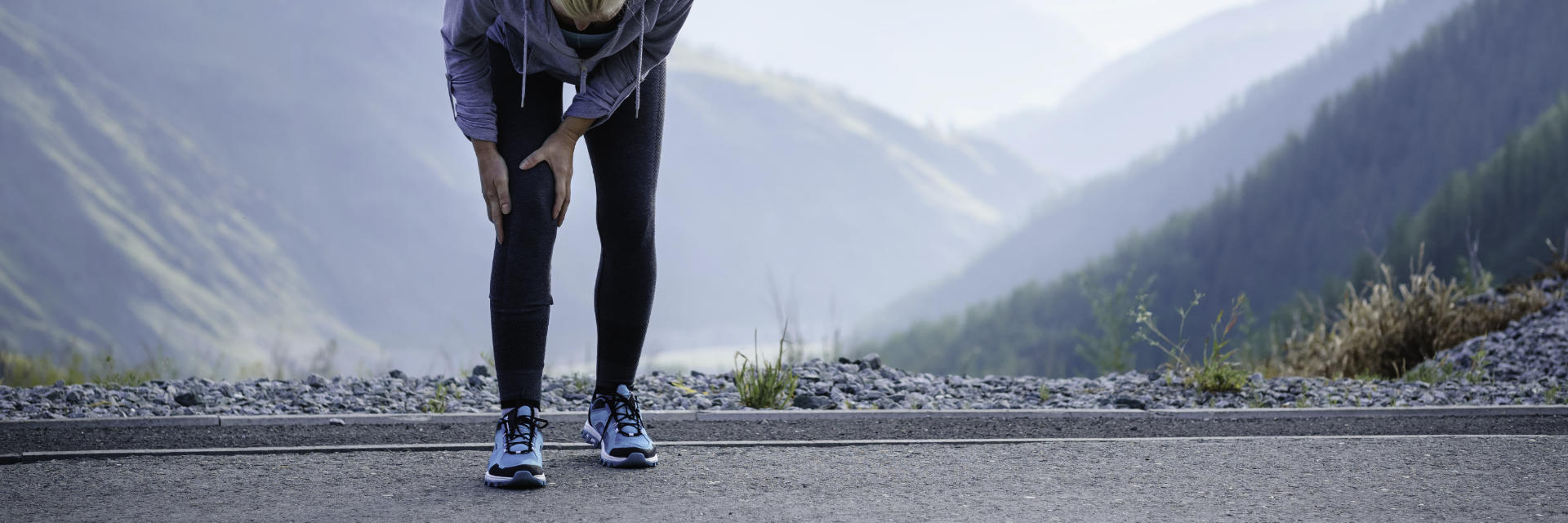 A woman running outdoors stopped by pain in the knee area.