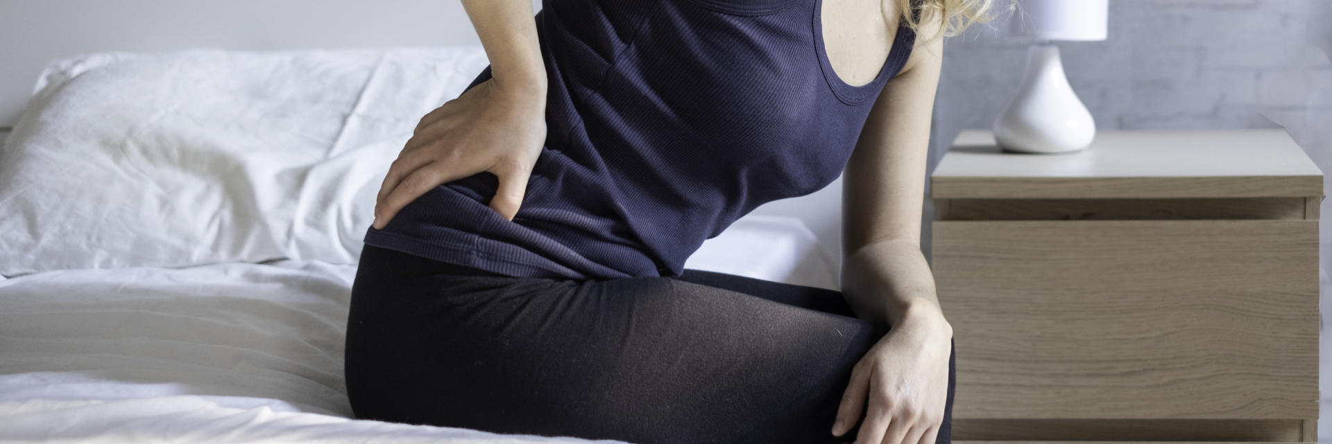 A woman feeling hip pain while trying to get up from the bed.