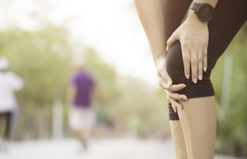 A woman running in the park stopped by sudden knee pain.