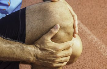 A runner holding his injured knee.