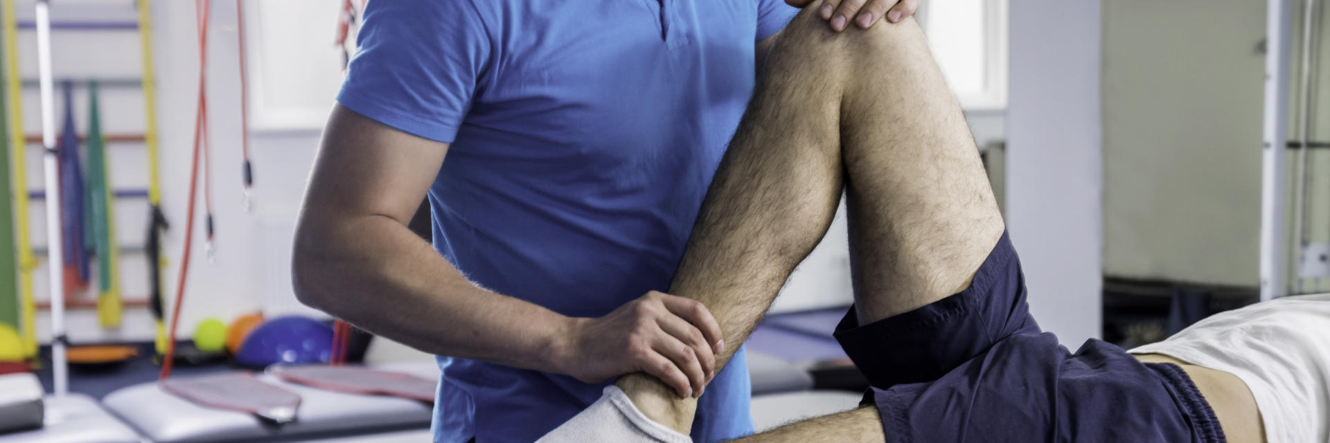 An orthopedic specialist examining patient's knee.