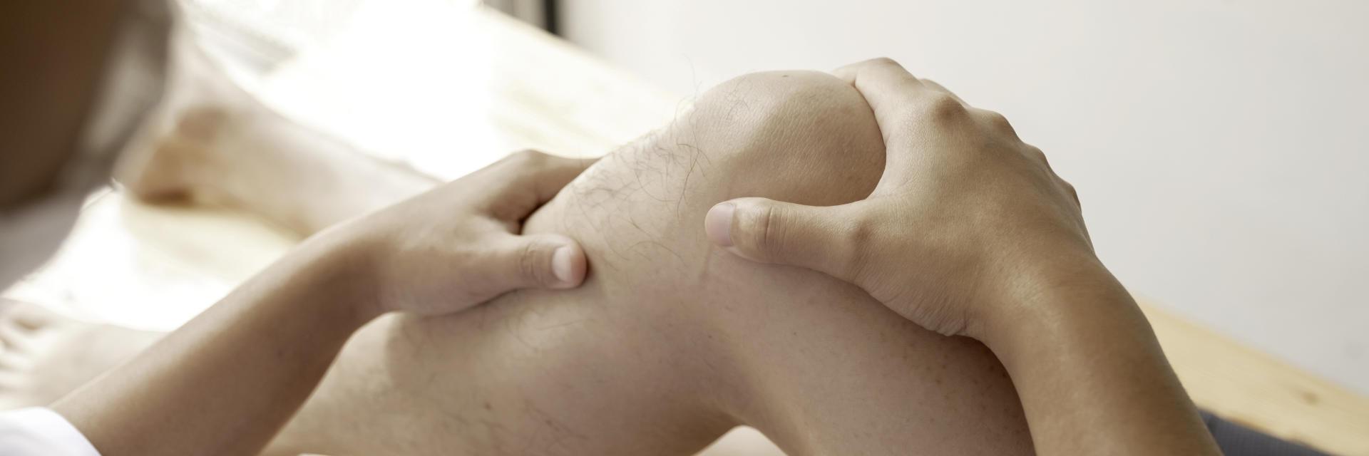 An orthopedic surgeon examining patient's knee.