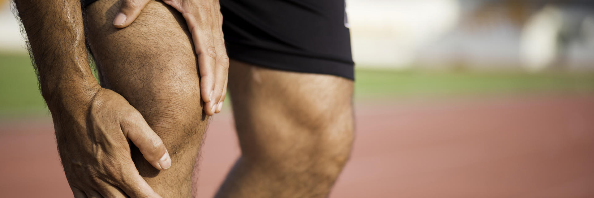 A sportsman touching the painful knee area.