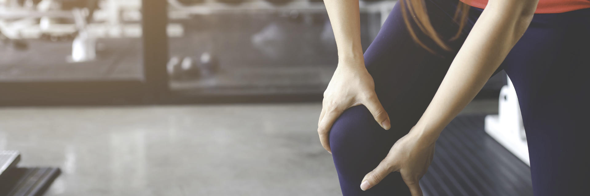 A woman holding her knee in pain due to injury she experienced while working out at the gym.