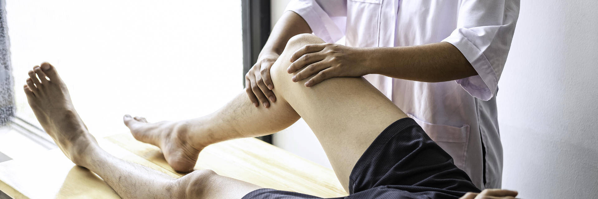 An orthopedic doctor examining patient's knee.