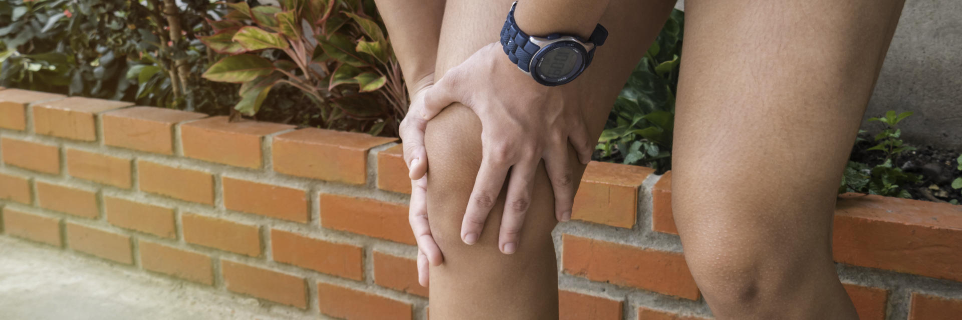 A person holding their knee in pain.