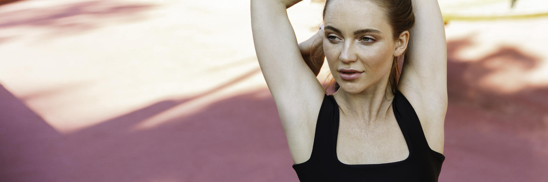 A sporty woman streaching her arms and shoulders.