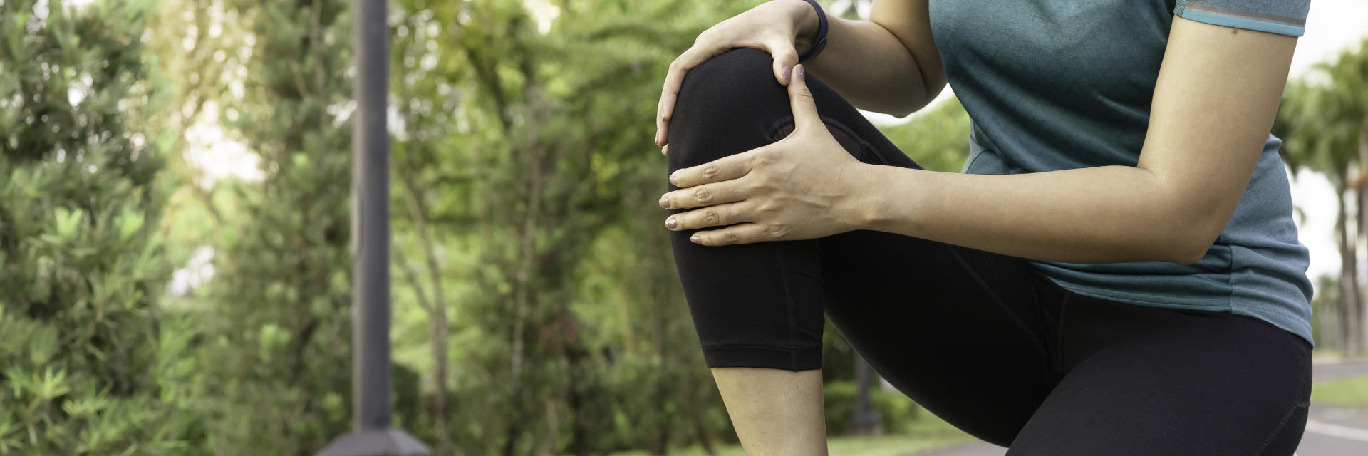 A woman running in the park stopped by pain in the knee area.